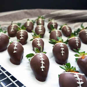 Chocolate-covered strawberry footballs from @bijouxandbits #superbowl #partyfood